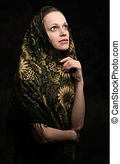 beautiful young woman in shawl looking up isolated on black...
