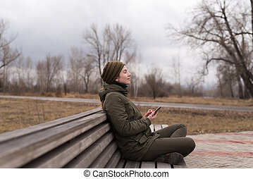 Woman with smartphone on a bench