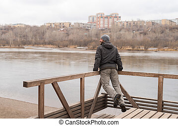 Man leaning on railing and jumping