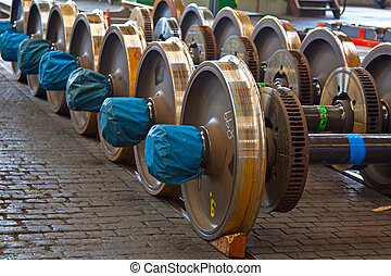 Spare railway wheels on the axle in a repair workshop