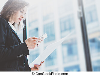 Photo business woman wearing suit, looking smartphone and holding documents in hands. Open space loft office. Panoramic windows background. Horizontal mockup. Film effect