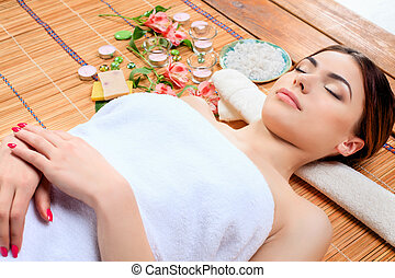 Beautiful young woman at a spa salon resting on a straw mat....
