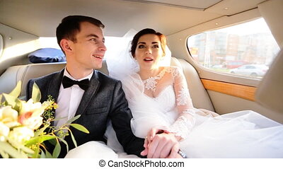 Bride and groom in love sitting on a car, holding hands and...