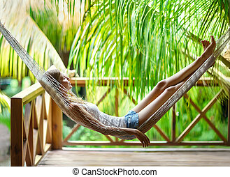 Young woman relaxing in hammock in a tropical resort - Young...