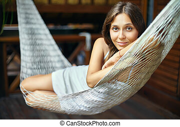 portrait of young beautiful woman lying in hammock in...