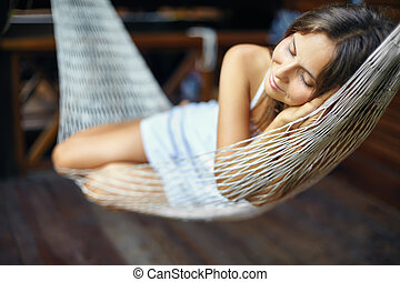 Young woman sleeping in a hammock - Young beautiful woman...