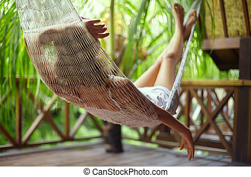 Young woman relaxing in hammock in a tropical resort.back...
