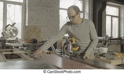Professional adult carpenter put polished wooden boards on working table.