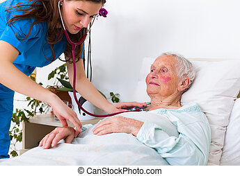 Geriatric examination - Young geriatrician doctor listening...