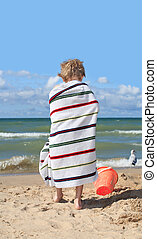 Child wrapped in a towel at the beach