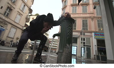 A man drinking fresh water from a fountain at Cannes street
