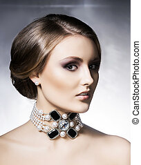 Young, beautiful and rich woman in jewels. Metal background