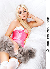 Hot and seductive blond in a pink corset and fur lying in...