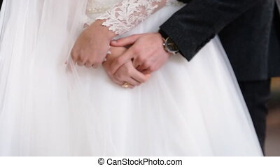 Close up of just married couple tenderly holding hands of each others.