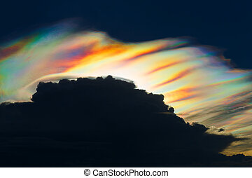 Iridescent cloud - Colorful iridescent cloud on dark sky in...