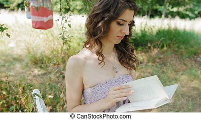 Young caucasian lady read a book outdoor in the park - Young...