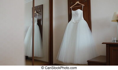 Fluffy wedding dress on a hanger in hotel room. Wedding...