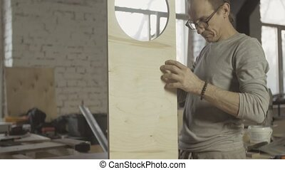 Professional carpenter connects two different wooden boards. Process of assembly