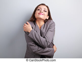 Happy business woman hugging herself with natural emotional...