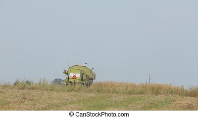 Combine green standing in a field - Combine in a gray shirt,...