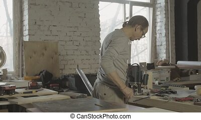 Professional carpenter take drill, process of making wooden furniture on table.