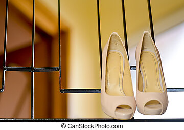 White stilleto bridal shoes hanging