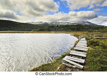 lake and wooden walkway with moutains on background - lake...