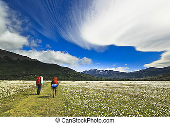 hikers going in patagonia mountains with beautiful clouds -...