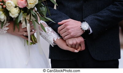 Close up of just married couple tenderly holding hands of...