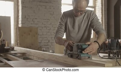 Aged woodworker careful treat wooden board by belt sander...