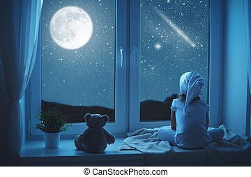 child little girl at window dreaming and admiring starry sky...