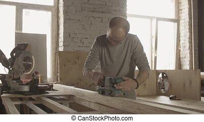 Woodworker in glasses treat wooden board by belt sander....