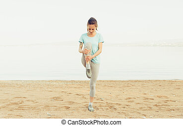 Sporty young woman stretching on beach
