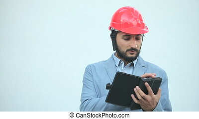 man in construction helmet make calculations on tablet
