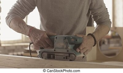 Aged woodworker careful process wooden board by belt sander...