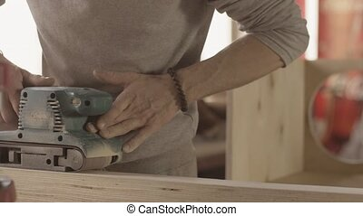 Aged woodworker careful process smooth of wooden board by...