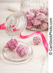 Homemade pink marshmallow on a white wooden background.