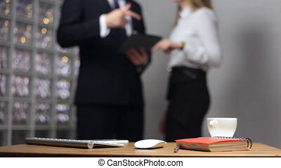 Documents on office table and man and woman talking in the...