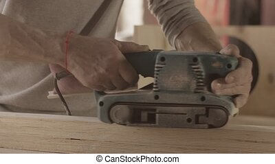 Carpenter careful process surface of wooden board by belt...