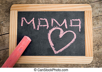 Old blackboard with Word Mama and a Heart, wooden table -...