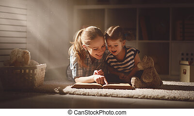 happy family mother and daughter read a book in evening -...