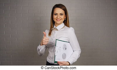 Businesswoman holding documents and showing thumb up -...