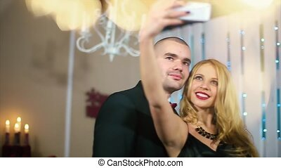 The woman in black evening dress takes photos with her phone a man in a black suit kisses her lips in the white room with the fireplace and Christmas tree