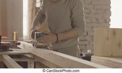 Joiner treats wooden board by belt sander. Move forward and...