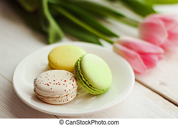 A beautiful flowers pink tulips with colorful macaroons laid...