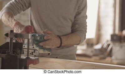 Carpenter treat wooden board belt sander Move forward...