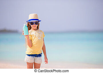 Little adorable girl with suntan lotion bottle on the beach...