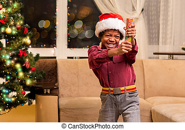 Afro boy holding Christmas petard. Little Santa with fire...