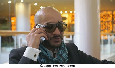 Arab businessman talking on mobile phone in hotel -...