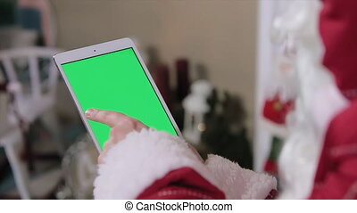 Santa Claus Using Digital Tablet Green Screen. Tablet with...